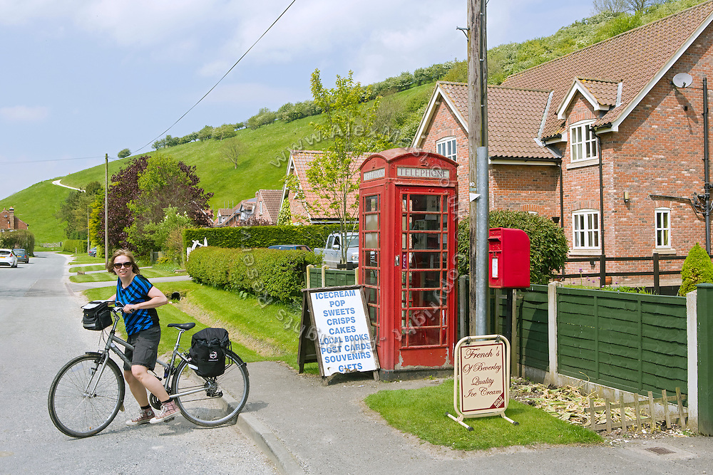 Next to a typical English red phone booth, a tourist is starting to cycle from Thixendale to York, in Yorkshire, England, United Kingdom.