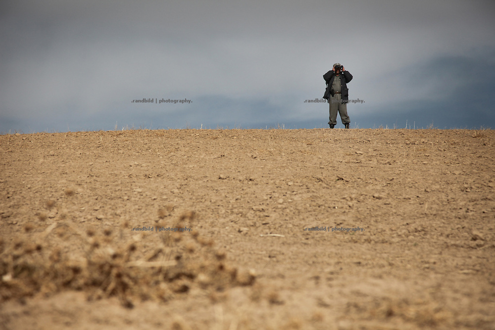 A police officer of the Afghan National Police (ANA) observs the surroundings from a hill in the Marmal mountain range.
