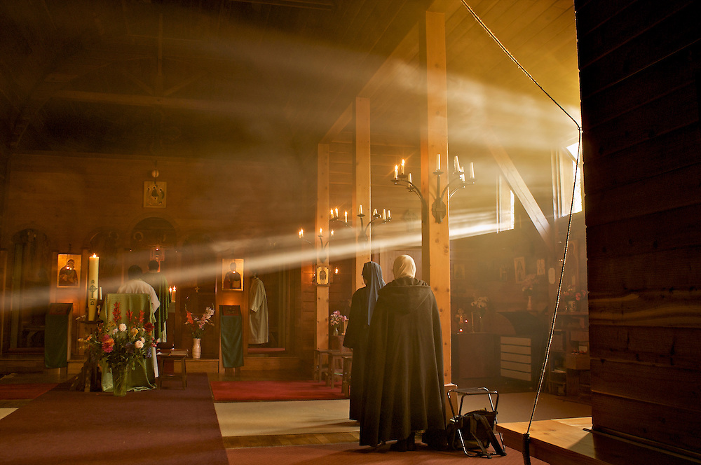 The Archbishop and monks at the Celtic Orthodox Monastery of Sainte-Dolay in Brittany.   Morning sunlight casts warm light though the incense of mass.