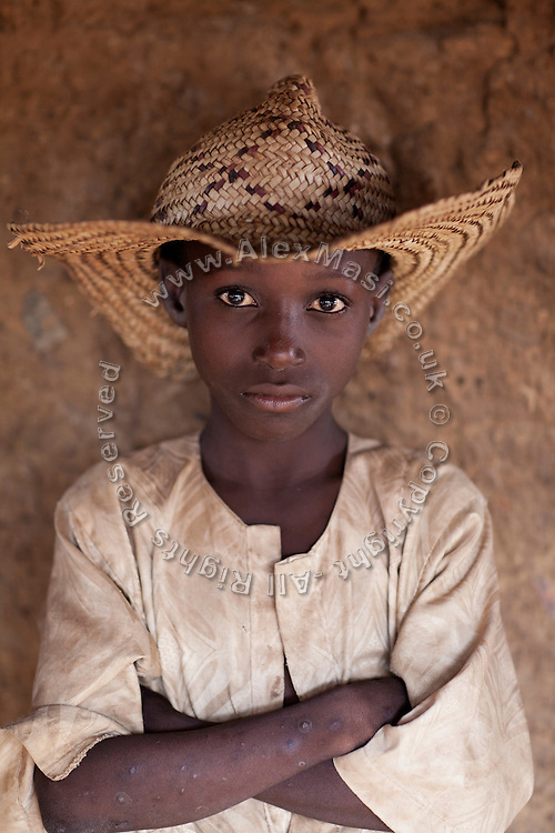 A boy is standing inside the affected village of Bagega, pop. 9000, Zamfara State, Nigeria, next to a large artisanal gold processing site. The lead contamination in the area is caused by ingestion and breathing of lead particles, released in the steps to isolate the gold from other metals. This type of lead is soluble in stomach acid and children under-5 are most affected, as they tend to ingest more through their hands by touching the ground, and are developing symptoms often leading to death or serious disabilities.