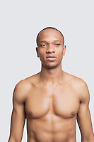Shirtless young man standing against gray background