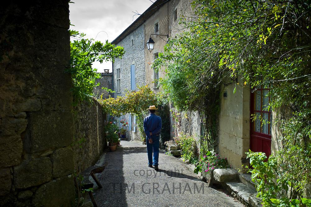 Man strolls in quaint town of Castelmoron d'Albret in Bordeaux region, Gironde, France