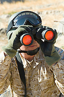 Soldier using binoculars outdoors (close-up)