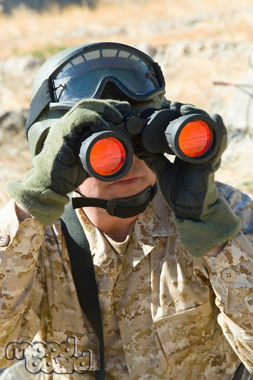 Soldier using binoculars outdoors (close-up)