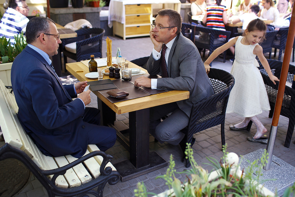 Ivan Mikloš, center, meets with Kálman Mizsei at La Veranda restaurant as a child plays nearby on May 25, 2015 in Kyiv, Ukraine. Mr. Mikloš is Chief Advisor to the Minister of Finance of Ukraine and Advisor to the Minister of Economic Development and Trade of Ukraine.