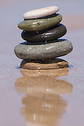 Small zen pebbles stacked on sand with a reflection in water.