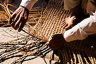 A man weaves a straw matt, slowly and meticulously by hand in a small village called, Bungamati, just south of Kathmandu,Nepal.