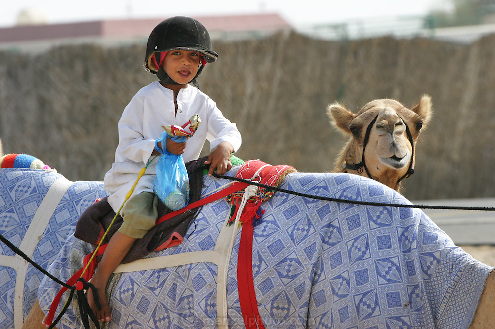A young boy jockey heads out for morning camel training at the Nad Al Sheba racecourse in Dubai with his breakfast snack of soda pop, chips, and candy. Although the practice of using children has been banned and declared illegal since 2002, young children from poor countries are still being used as jockeys because of their light weight and low cost. (Supporting image from the project Hungry Planet: What the World Eats).