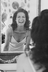 Woman looking  at herself in the mirror and laughing