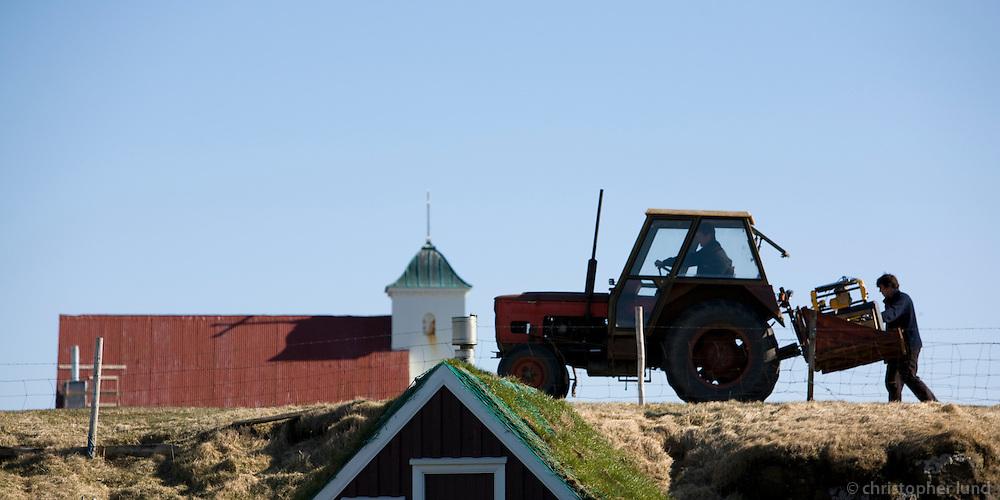Frá Flatey, fólk að flytja pressu á dráttavél. Flateyjarkirkja í baksýn..From island Flatey, People transporting a machine on a Tractor, the church in background.