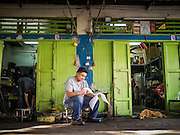 20 APRIL 2013 - BANGKOK, THAILAND:   A man does paperwork in front of his mechanical shop in Talat Noi (Talat means Market, Noi means Small. Literally Small Market). The Talat Noi neighborhood in Bangkok started as a blacksmith's quarter. As cars and buses replaced horse and buggy, the blacksmiths became mechanics and now the area is lined with car mechanics' shops. It is one the last neighborhoods in Bangkok that still has some original shophouses and pre World War II architecture. It is also home to a  Teo Chew Chinese emigrant community.   PHOTO BY JACK KURTZ