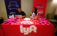 Recruiters for Lyft wait for the opening of a job fair in Golden, Colorado June 7, 2016. REUTERS/Rick Wilking