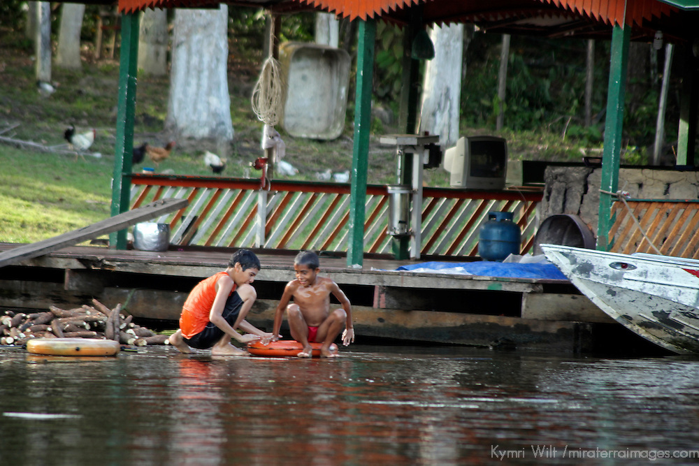 South America, Brazil, Amazon. Two boys pass the time on the riverbank and keep cool.