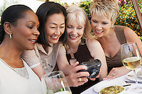 Four elegant women at garden party looking at photos on digital camera