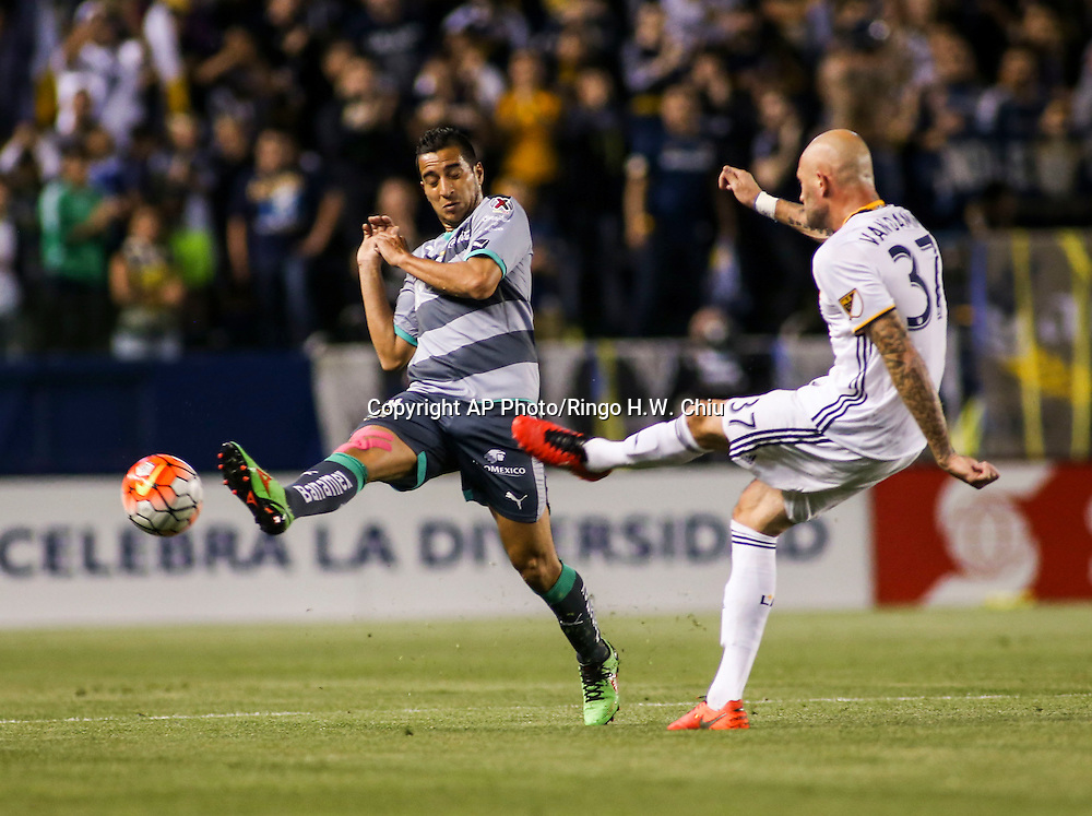 Los Angeles Galaxy's defender Jelle Van Damme, right, shoots the ball against Santos Laguna's midfielder Diego Gonzalez during the first half of a CONCACAF Champions League quarter final game in Carson, Calif., Wednesday, Feb. 24, 2016. (AP Photo/Ringo H.W. Chiu)