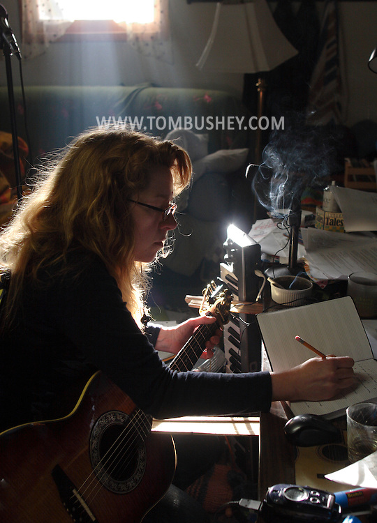 Middletown, NY - Singer and songwriter Elizabeth Bushey works on a song with her guitar in her basement studio on May 10, 2008.
