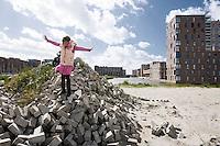 Nederland Amsterdam 15-09-2010 20100915..Nieuwbouw wijk IJburg, woningen in het hogere segment. Meisje speelt  op braakliggend terrein met stapels bakstenen dat nog bebouwd zal gaan worden.  IJburg is een woonwijk in aanbouw in het oosten van de gemeente Amsterdam, in de Nederlandse provincie Noord-Holland. Kenmerkend aan de in het IJmeer gelegen wijk is dat deze op kunstmatige eilanden is gebouwd. IJburg maakt onderdeel uit van het stadsdeel Oost. Holland, The Netherlands, dutch, Pays Bas, Europe , Yburg, het Ij, Het Y, , gebiedsontwikkeling, waterwijk, waterwijken, waterwoning, waterwoningen, wijk, wijken, wonen aan het water, woning, woningaanbod, woningbouw, woningen, woningmarkt, woningvoorraad, woonbuurt, woonbuurten, woonlast, woonlasten, woonwijk, woonwijkent, toekomstige plannen, uitbreidingsgebieden, vastgoed, vernieuwing, vernieuwing stedelijk, verstedelijking, vessel, vinex, vinex-locaties, vinex-wijken, vinexbuurt, vinexlocatie, vinexlokatie, vinexwijk, volkshuisvesting, voorgevel, water, woning, woningaanbod, woningbehoefte, woningblok, woningblokken, woningbouw, woningen, woningkopers, woningmarkt, woningvoorraad, woonblok, woonblokken, woongebied, woonlast, woonlasten, zichzelf vermaken..Foto: David Rozing