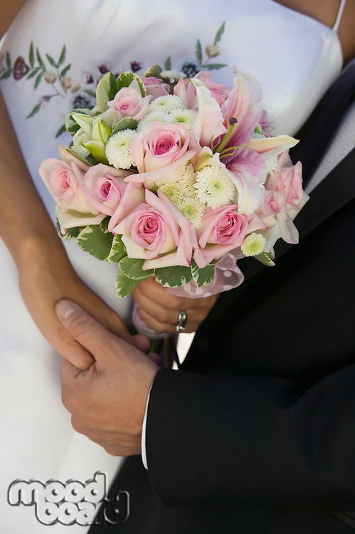 Bride and Groom Holding Hands and Bouquet