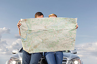 Couple reading map while leaning on car hood during road trip