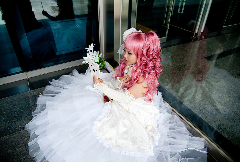 A girl dressed as a character from the song program Vocaloid looks into a mirror at Busan Comic World, a bi-monthly comic convention in Busan, South Korea, May 5, 2012.