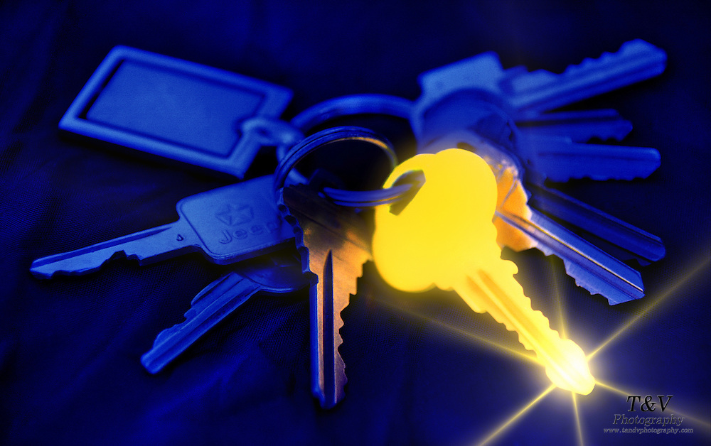 Key ring with several keys, including one that glows a golden yellow and is highlighted with a star.Black light