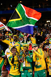 Fans of South Africa waving a flag and blowing on horns