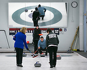 Richard Dimperio (center, kneeling) gives instructions to teammates Carol Della Villa and Megan Klein as Caitlin Maroldo (center, standing) looks on during a match at Rochester Curling Club on Sunday, February 8, 2015.