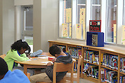 Natural lighting streams in through windows that reach the ceiling in the library at Billy Reagan K-8 School.