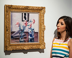 "© Licensed to London News Pictures. 18/11/2016. London, UK. A staff member views ""Pink Carnations"" by Francis Campbell Boileau Cadell (est. GBP200-300k), at the preview at Sotheby's of works on view at four upcoming November auctions featuring Modern & Post-War British Art, A Painter's Paradise (Julian Trevelyan & Mary Fedden at Durham Wharf), Scottish Art and Picasso Ceramics from the Lord & Lady Attenborough Private Collection. Photo credit : Stephen Chung/LNP"