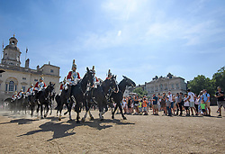 © Licensed to London News Pictures. 06/08/2018. London, UK.  Tourists watch the changing of the Guard ceremony on horse Guards Parade in central London as hot weather continues in the capital. Photo credit: Ben Cawthra/LNP