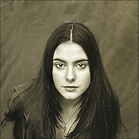 A young woman with long dark hair staring at the camera