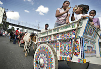 Unidentified girls eat ice cream while attend to the 9th parade of the traditional oxcart in  San Jose, Costa Rica on Saturday November 27, 2005. These kind of painted oxcart is a symbol of the folk culture in Costa Rica. UNESCO recognize this cars as Humankind Nonmaterial Patrimony. Hundred of oxcarts participated in this parade. (Photo/Cristobal Herrera)