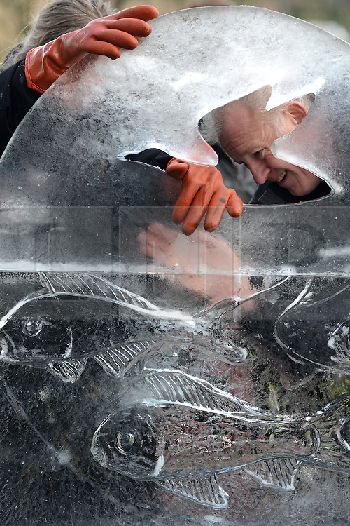 © Licensed to London News Pictures.10/01/2013. London, UK. Members of team Belgium a create an ice sculpture during the single block ice-sculpting competition at the London Ice Sculpting Festival in Canary Wharf.. Photo credit : Peter Kollanyi/LNP