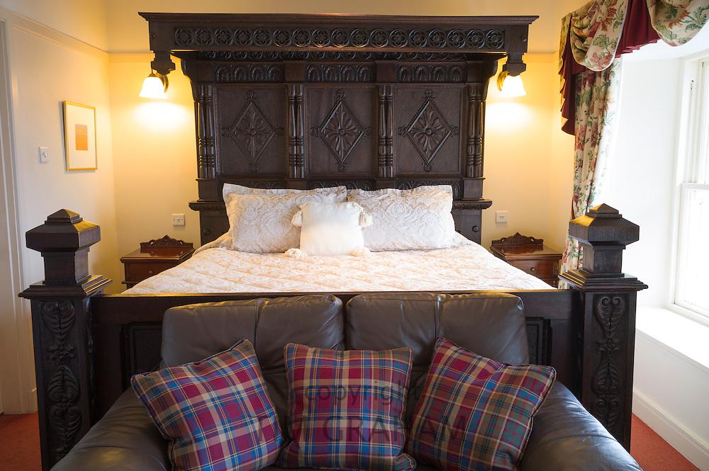 Oak bed in stylish bedroom with tartan furnishings at luxurious upmarket Ullinish Lodge Hotel at Struan, Isle of Skye, Western Isles of Scotland