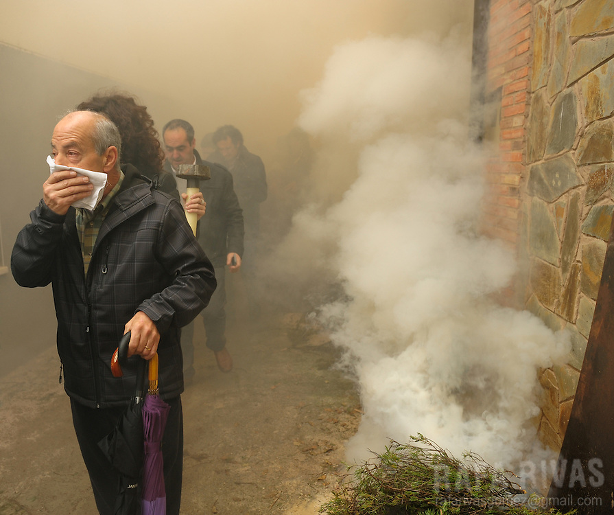 "People take part during the ""Procession of smoke"" on November 25, 2012, in the northern Spanish village of Arnedillo. Locals light bonfires to produce smoke that covers Arnedillo streets while the patron saint San Andres is carried in procession."