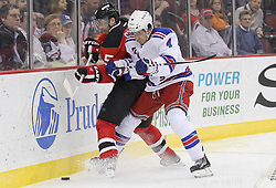 Mar 6; Newark, NJ, USA; New York Rangers defenseman Michael Del Zotto (4) and New Jersey Devils right wing Petr Sykora (15) battle for the loose puck during the second period at the Prudential Center.