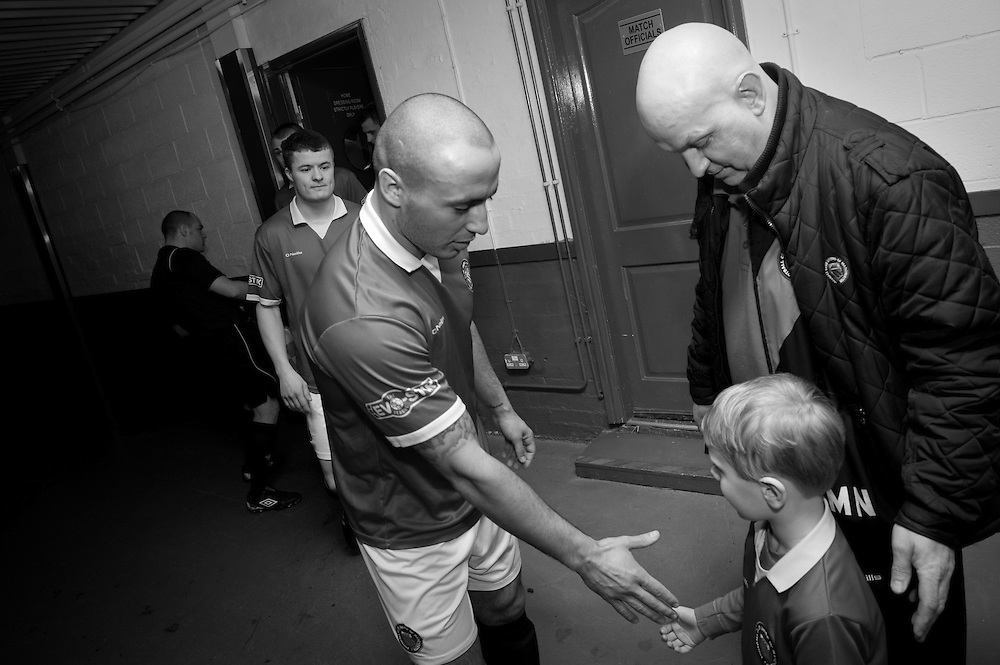 FC United of Manchester play a local team Chorley at Bury football club's ground in Lancashire, Britain. Photo shows FC United of Manchester player shaking hands with a young team mascot before the match.