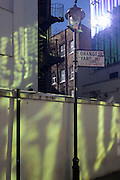 Green light from a nearby office building is reflected onto plain walls in Orange Yard, Soho, central London.