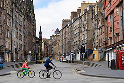 Edinburgh, Scotland, UK. 18 April 2020. Views of empty streets and members of the public outside on another Saturday during the coronavirus lockdown in Edinburgh. Family cycling past the Royal Mile. Iain Masterton/Alamy Live News