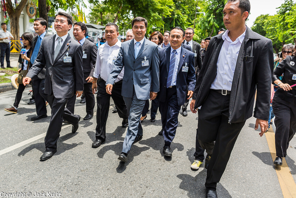 07 AUGUST 2013 - BANGKOK, THAILAND: Former Thai Prime Minister ABHISIT VEJJAJIVA, center, walks with members of his party to the Thai Parliament building during anti-amnesty protests in Bangkok. Abhisit's party, the Democrats, organized the anti-amnesty protest. About 2,500 protestors opposed to an amnesty bill proposed by Thailand's ruling party marched towards the Thai parliament in the morning. The amnesty could allow exiled fugitive former Prime Minister Thaksin Shinawatra to return to Thailand. Thaksin's supporters are in favor of the bill but Thai Yellow Shirts and government opponents are against the bill. Thai police deployed about more than 10,000 riot police and closed roads around the parliament. Although protest leaders called off the protest rather than confront police, a few people were arrested for assaulting police when they tried to break through police lines. Several police officers left the scene under medical care after they collapsed in the heat.    PHOTO BY JACK KURTZ