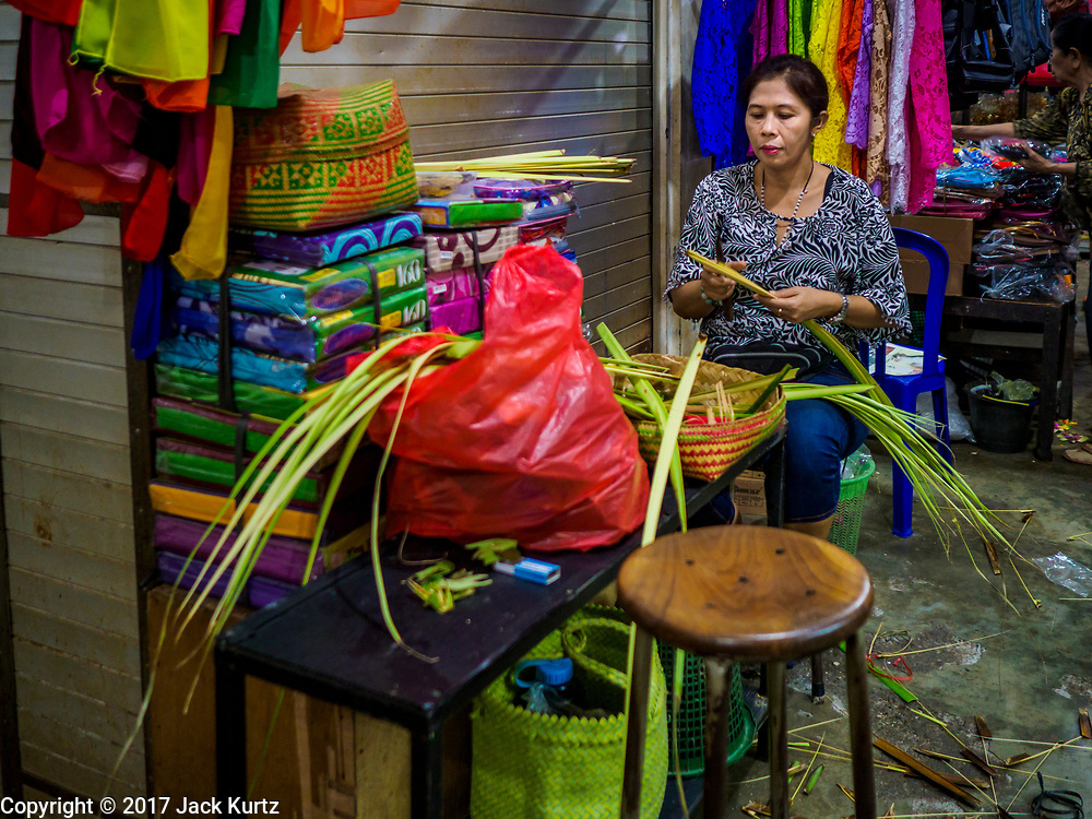 03 AUGUST 2017 - SUKAWATI, BALI, INDONESIA: A vendor makes baskets for offerings in the market in Sukawati. Bali's local markets are open on an every three day rotating schedule because venders travel from town to town. Before modern refrigeration and convenience stores became common place on Bali, markets were thriving community gatherings. Fewer people shop at markets now as more and more consumers go to convenience stores and more families have refrigerators.    PHOTO BY JACK KURTZ