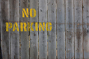 Detail of a No Parking stencil lettering on wooden slats in south London.