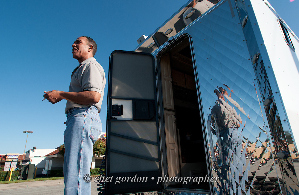 Over the road driver Jose Williams has a smoke outside his sleeper compartment in Castroville, CA on Sunday morning, April 26, 2015. Williams, a cross country trucker with a national household moving company, made several delivery stops in central California's Bay Area during the week with loads that originated in Virginia on April 16th.  © Chet Gordon/THE IMAGE WORKS