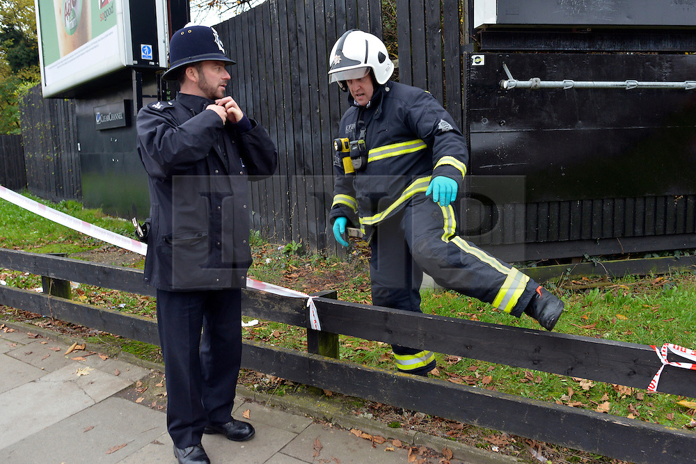 © Licensed to London News Pictures. 16/11/2012. Streatham, UK Police and Fire officers at the scene. The fire took place behind an advertising hoarding. Two people have died and another is in hospital with burns after a fire on wasteland in south London. Firefighters were called to the scene in Streatham High Road, Streatham, just after 02:20 GMT. Two bodies were found at the scene and a third person was taken to hospital for treatment. Crews took just over an hour to bring the fire under control. The incident is being investigated by the London Fire Brigade and the Metropolitan Police. Photo credit : Stephen Simpson/LNP