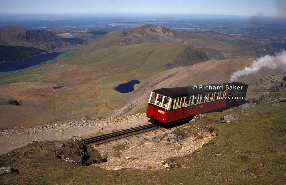 The rack and pinion narrow guage mountain railway nearing the summit of Mount Snowdon, the highest point in England, on 14th June 1992, in Llanberis, Wales, UK. The rack and pinion system used is that patented by the Swiss engineer Dr Roman Abt. The railway uses double rack rails, fastened to steel sleepers between the running rails. Each locomotive is equipped with toothed pinions (cogwheels), which engage the rack and provide all the traction necessary to scale the steepest inclines. On the way down, the rack and pinion system also acts as a brake.