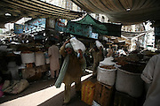 A Pukhtun laborer carries bags full of grain at a wholesale market in Karachi, Pakistan.