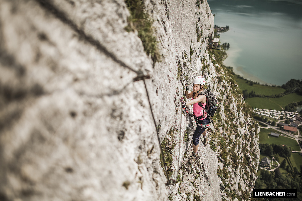 young woman climbs a via ferrata in Mondsee/Austria