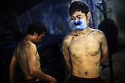 "Workers take a dawn break after scrubbing jeans all night using a sanding machine in Mr Huang's factory in Zhongshan city, China. The blue dust from the jeans is a heavy irritant to the lungs. .This picture is part of a photo and text story on blue jeans production in China by Justin Jin. .China, the ""factory of the world"", is now also the major producer for blue jeans. To meet production demand, thousands of workers sweat through the night scrubbing, spraying and tearing trousers to create their rugged look. .At dawn, workers bundle the garment off to another factory for packaging and shipping around the world..The workers are among the 200 million migrant labourers criss-crossing China.looking for a better life, at the same time building their country into a.mighty industrial power."