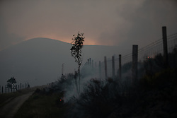 "© Licensed to London News Pictures . 27/06/2018 . Saddleworth , UK . Heavy smoke fills the air for miles around . Homes are evacuated and a Major Incident is declared as fire-fighters work to control large wildfires spreading across Saddleworth Moor and towards residential areas in surrounding towns . Very high temperatures , winds and dry peat are hampering efforts to contain the fire , described as "" unprecedented "" by police and reported to be the largest in living memory . Photo credit : Joel Goodman/LNP"