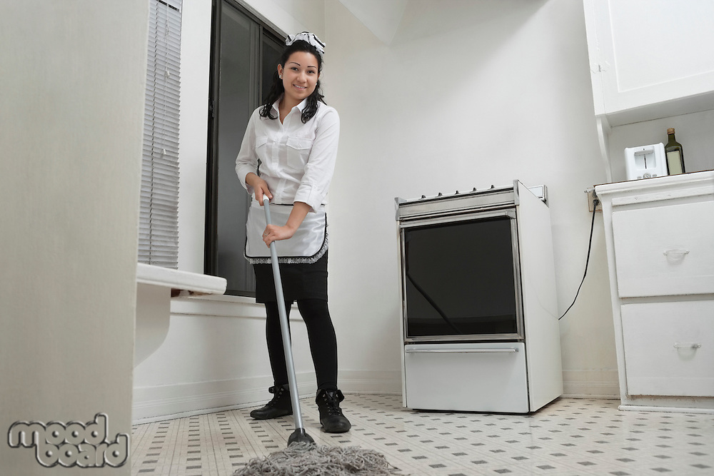 Full length portrait of young housemaid cleaning floor with mop